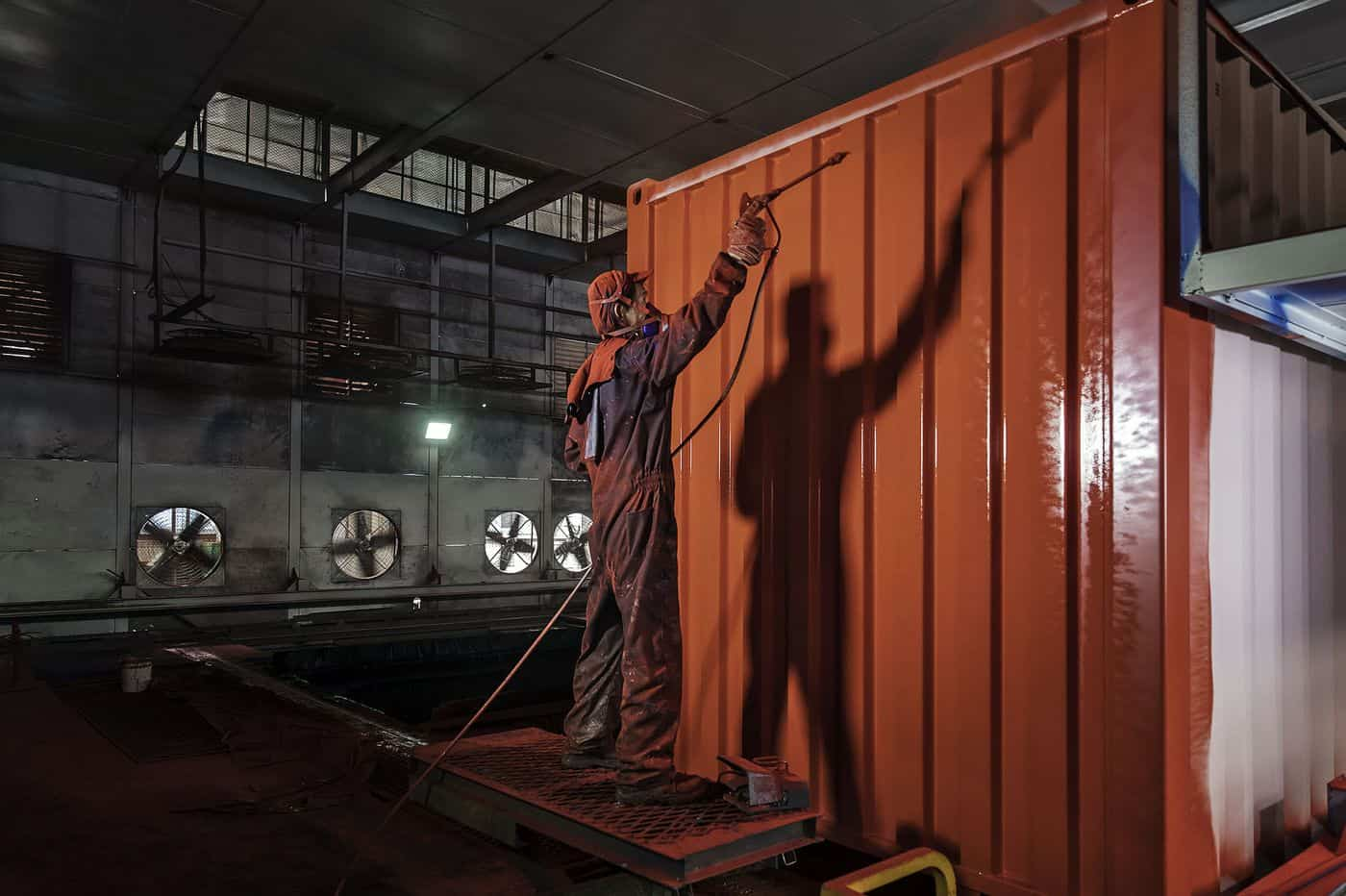 Ouvrier peignant un container